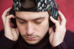 Retrato da música de escuta do homem novo através dos fones de ouvido Fotos de Stock