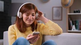 Retrato da música do canto da menina, mulher caucasiano nova que relaxa, sentando-se no sofá e escutando a música em casa Bonito filme