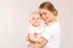 Retrato da m?e feliz com seu beb? contra luzes borradas fotos de stock