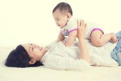 Retrato da mamã bonita que joga com seus 6 meses do bebê idoso dentro Fotografia de Stock Royalty Free