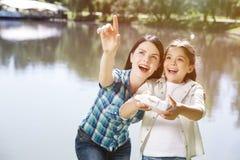 Retrato da mamã e da criança que estão junto perto da lagoa e que olham acima A mulher está apontando acima A menina é controle d Imagem de Stock