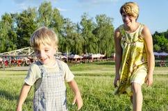 Retrato da mamã feliz que joga com seu filho do bebê no jardim verde do verão Fotos de Stock Royalty Free