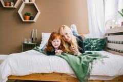 Retrato da mamã nova e da filha pequena do ruivo que encontram-se na cama fotos de stock
