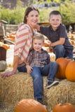 Retrato da mãe atrativa e dos seus filhos no remendo da abóbora Foto de Stock Royalty Free