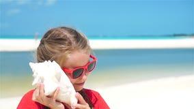 Retrato da menina adorável pequena que escuta uma concha do mar grande na praia Movimento lento video estoque