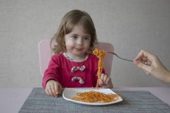 Retrato da menina adorável que come os espaguetes que sentam-se na tabela Imagens de Stock