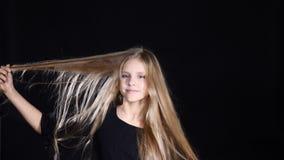 Retrato da menina adorável que levanta olhando a câmera Sorrindo e tocando em seu cabelo Menina adolescente bonita loura com cabe filme