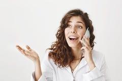 Retrato da menina adulta europeia atrativa entusiasmado com corte de cabelo na moda que fala no telefone celular ao gesticular e  fotografia de stock