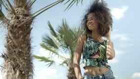 Retrato da menina afro-americana adolescente bonita na praia tropical que sorri a uma câmera filme