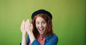 Retrato da menina alegre que joga o esconde-esconde que sorri no fundo verde video estoque