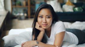 Retrato da menina asiática bonita no t-shirt branco que encontra-se na cama confortável com folhas brancas, sorrindo e olhando filme