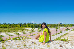 Retrato da menina asiática bonita nova que senta-se na parte superior do monte que enfrenta a câmera Fotos de Stock Royalty Free