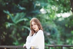 Retrato da menina asiática do moderno novo que levanta no fundo da floresta do parque imagem de stock royalty free