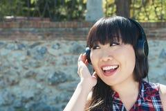Retrato da menina atrativa nova que escuta a música com headph imagens de stock royalty free