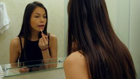 Retrato da menina atrativa nova que rouging seus bordos e que sorri a sua reflexão Fotografia de Stock