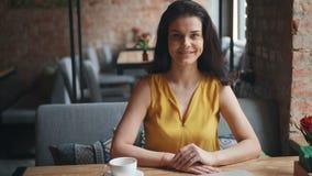 Retrato da menina atrativa que senta-se no café com a bebida que olha o sorriso da câmera