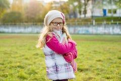 Retrato da menina aucasian adorável 7 anos velha, com cabelo encaracolado longo louro, nos vidros e em um tampão feito malha Imagens de Stock