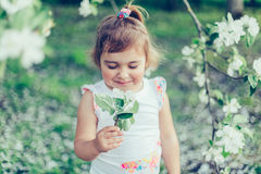 Retrato da menina bagunçado bonito pequena que ri e que tem o divertimento fora entre árvores de florescência em um dia de verão  Foto de Stock Royalty Free