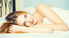 Retrato da menina bonita acordado na cama