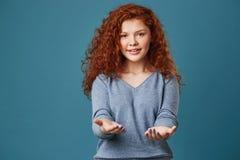 Retrato da menina bonita com cabelo e as sardas vermelhos ondulados na camisa cinzenta que puxa as mãos in camera com feliz e o r Imagem de Stock