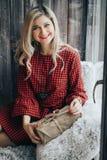 Retrato da menina bonita de sorriso com cabelo encaracolado louro e o sorriso surpreendido que guardam suas mãos perto da cara imagem de stock