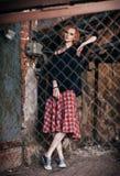 Retrato da menina bonita do grunge na saia e na camiseta de manta que estão atrás da estrutura metálica imagem de stock