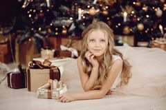 Retrato da menina bonita na árvore de Natal branca do fundo do vestido fotos de stock