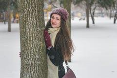 Retrato da menina bonita na neve que esconde atrás de uma árvore foto de stock