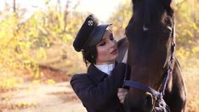 Retrato da menina bonita na roupa e no chapéu especiais com o cavalo marrom no outono filme