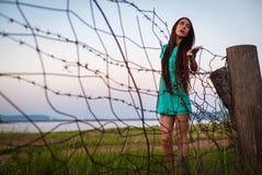 Retrato da menina bonita nova em um vestido de turquesa perto do arame farpado no verão exterior imagens de stock royalty free