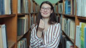 Retrato da menina bonita nova na biblioteca Estudante fêmea que estuda entre o lote dos livros entre shelfs A menina fala filme