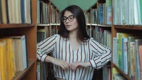 Retrato da menina bonita nova na biblioteca Estudante fêmea que estuda entre o lote dos livros entre shelfs filme