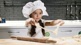 Retrato da menina bonita pequena no chapéu do cozinheiro chefe que joga com massa, cozinheiro da criança na cozinha real 4K video estoque