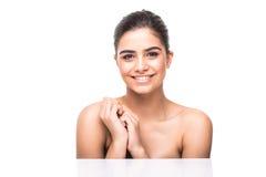 Retrato da menina bonita que afaga sua cara bonita com fundo saudável do branco da pele imagens de stock