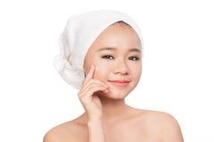 Retrato da menina bonita que aplica o creme na cara - isolada no branco Fotos de Stock Royalty Free
