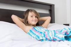 Retrato da menina bonita que encontra-se na cama foto de stock