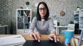 Retrato da menina bonita que usa o assento de datilografia do portátil no escritório que trabalha apenas
