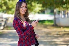 Retrato da menina bonita que usa seu telefone celular na cidade Imagens de Stock Royalty Free