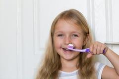 Retrato da menina bonito com cabelo louro que dente de limpeza com escova e dent?frico no banheiro imagem de stock royalty free