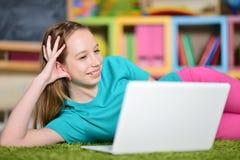 Retrato da menina bonito com o laptop no assoalho fotos de stock