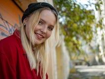 Retrato da menina bonito nova de sorriso no chapéu feito malha que está fora perto da parede foto de stock