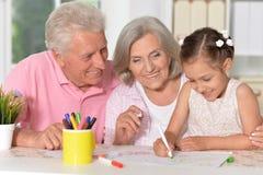 Retrato da menina bonito pequena com as avós que tiram na tabela imagens de stock royalty free