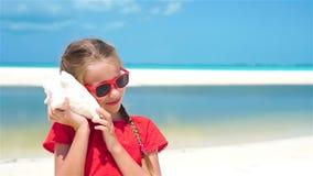Retrato da menina bonito pequena que escuta uma concha do mar grande na praia Movimento lento filme