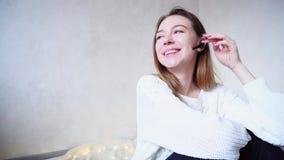 Retrato da menina bonito que através dos auriculares do bluetooth com sorriso conversa, sentando-se no assoalho na manta na sala  filme