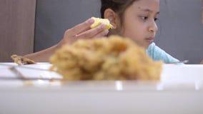 Retrato da menina bonito que come algum alimento na tabela durante o tempo do almoço filme