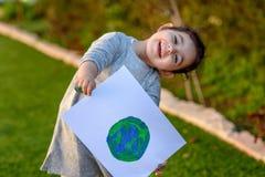 Retrato da menina bonito que guarda o globo de tiragem da terra Drawng da criança uma imagem da terra imagem de stock royalty free