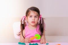 Retrato da menina bonito que joga com os brinquedos para o playdough foto de stock