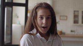 Retrato da menina bonito que olha a câmera que sorri felizmente e que mostra a surpresa em sua cara em casa carefree vídeos de arquivo