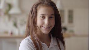 Retrato da menina bonito que olha a câmera que sorri felizmente Inf?ncia despreocupada Pouco menina emocional em casa real filme