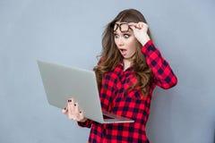 Retrato da menina chocada com boca aberta usando o portátil fotos de stock royalty free